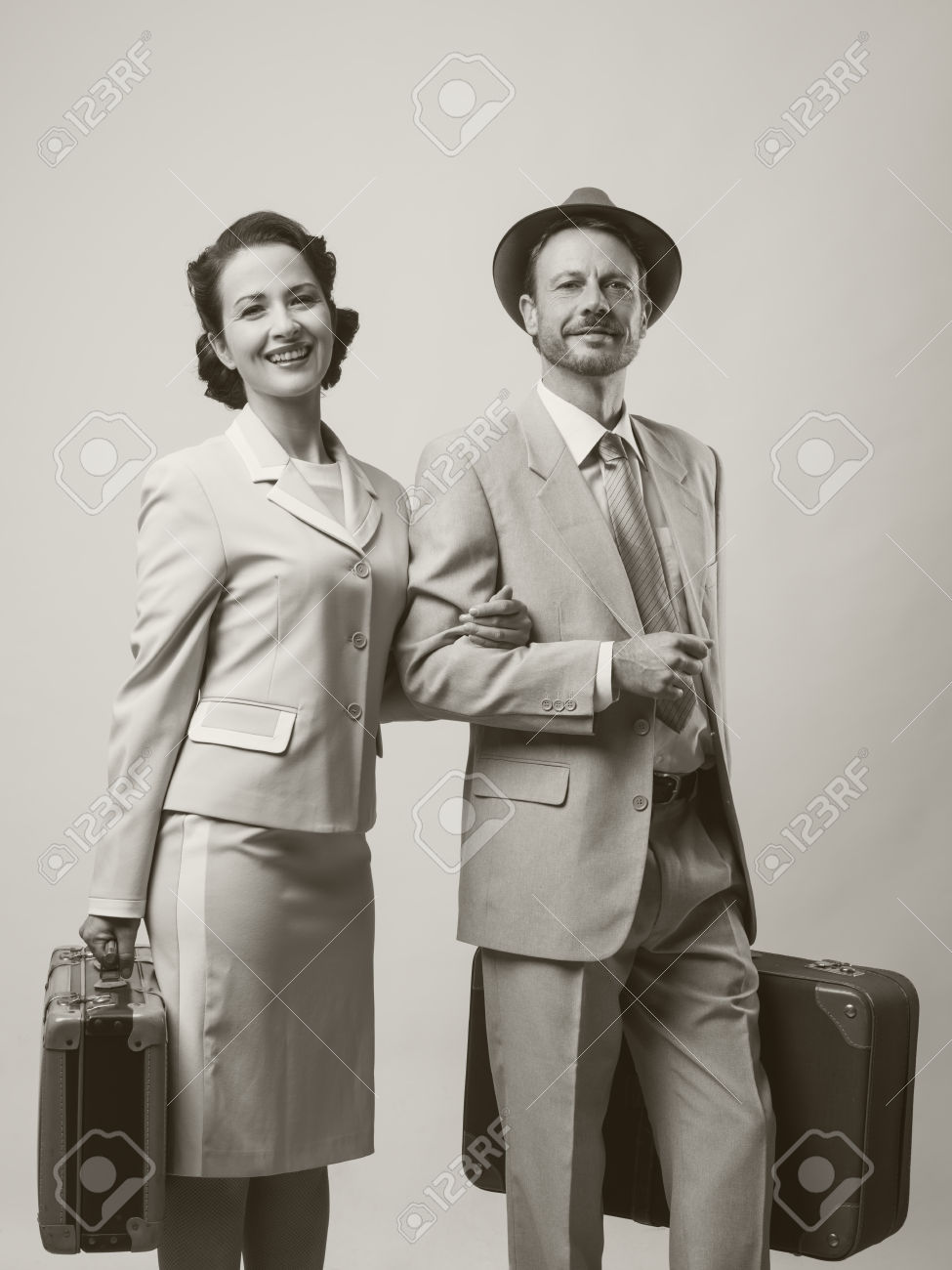 Elegant loving couple leaving for honeymoon with luggage, 1950s style